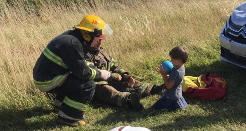 Se viralizó una foto de dos Bomberos que juegan con un pequeño mientras rescataban a sus padres del interior de un vehículo accidentado