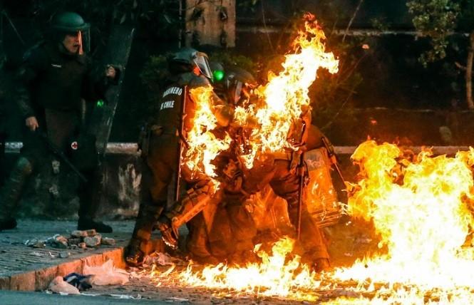 Las impactantes imágenes de carabineros envueltos en llamas tras ser atacados con bombas molotov en Chile